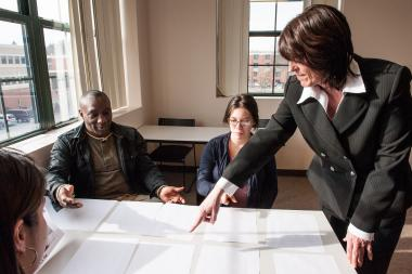 QCC instructor discusses topic with students at desk