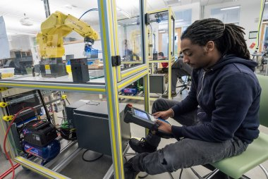 Student works with robot in manufacturing lab