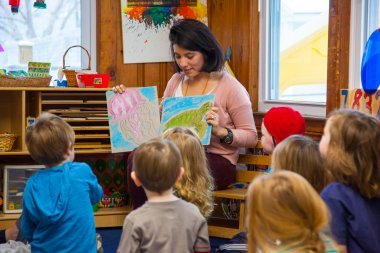 An instructor in the Children's School reads to students