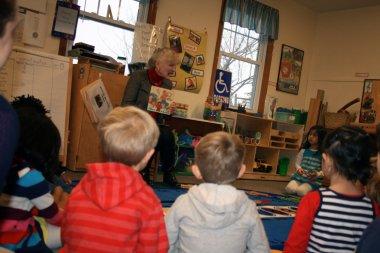 Staff member reading to children in Children's School