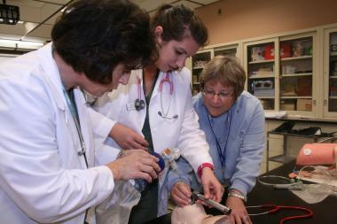 QCC students practice healthcare techniques on dummy