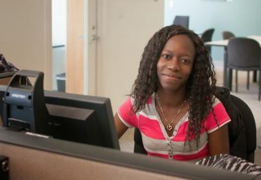 QCC student at computer desk