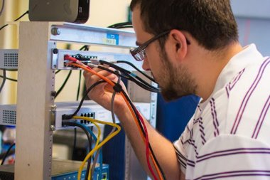 QCC Student connects wires to server