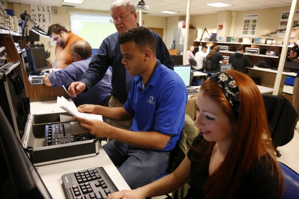 QCC Professor demonstrates hardware to students in lab