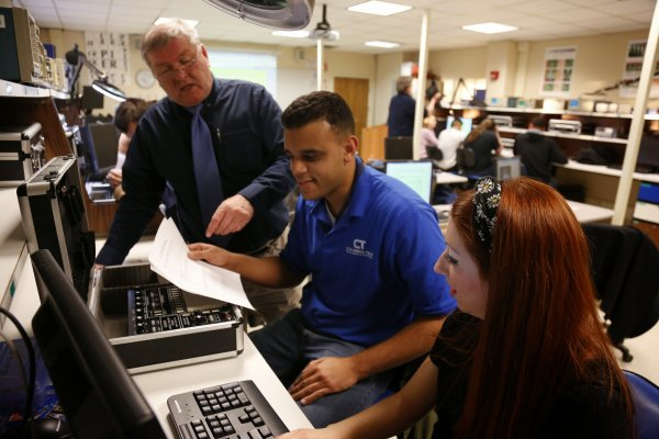 QCC instructor demonstrates computer hardware to students