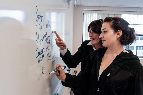 QCC student and instructor at whiteboard