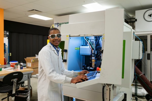Man stands at machine using lasers