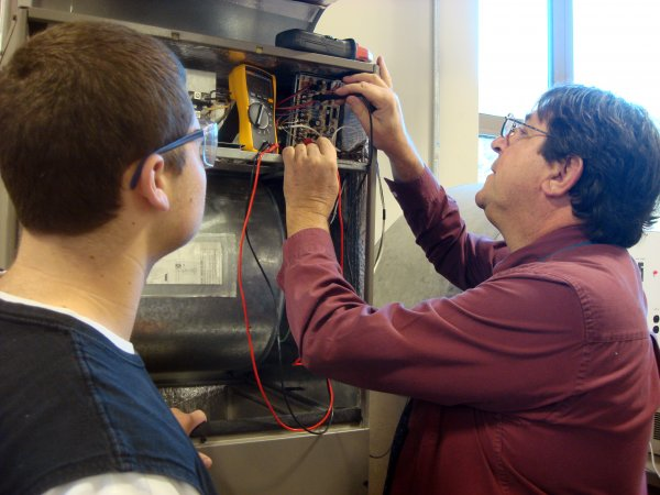 QCC professor and student work on air conditioner