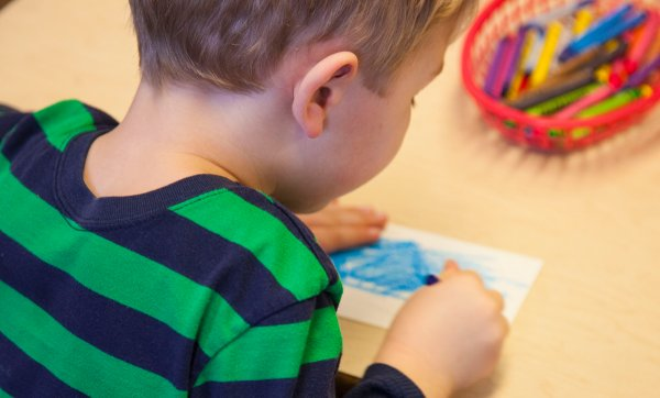 Child from QCC's Children's School draws picture