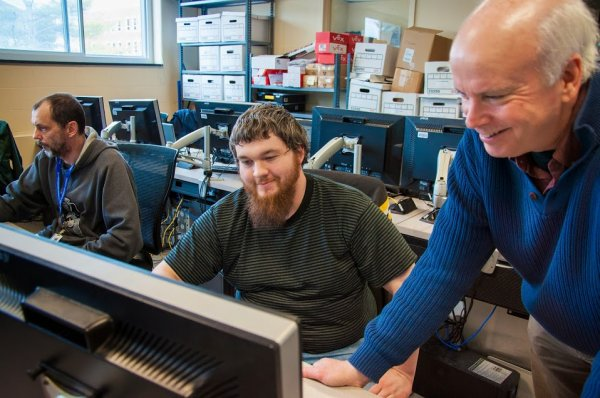 QCC Professor helps students in computer lab