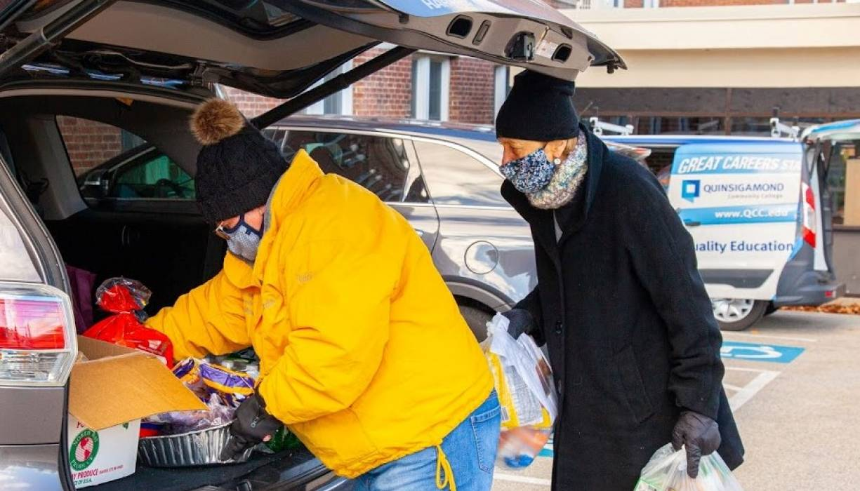 From left: Dean of Compliance Liz Woods and QCC Foundation President Dr. Linda Maykel help load food into a student's vehicle.