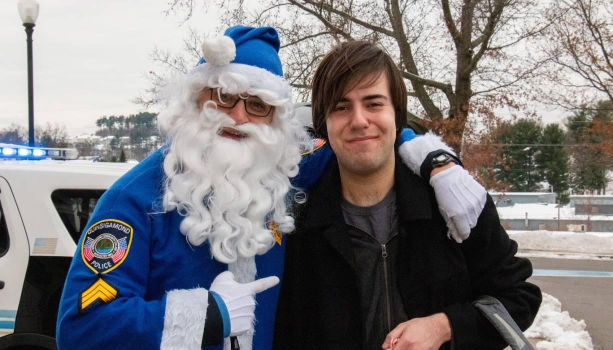 Blue Santa gives a holiday greeting to QCC student George Baraklilis.