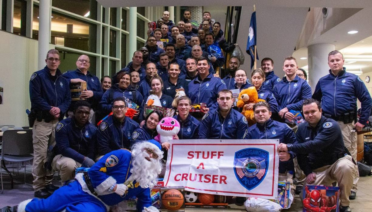 QCC Police Academy students make a large donation on Dec. 9 to the Stuff-A-Cruiser event.