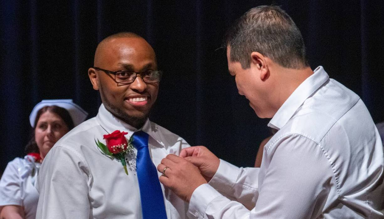 A QCC Practical Nursing grad is all smiles as he gets his pin.