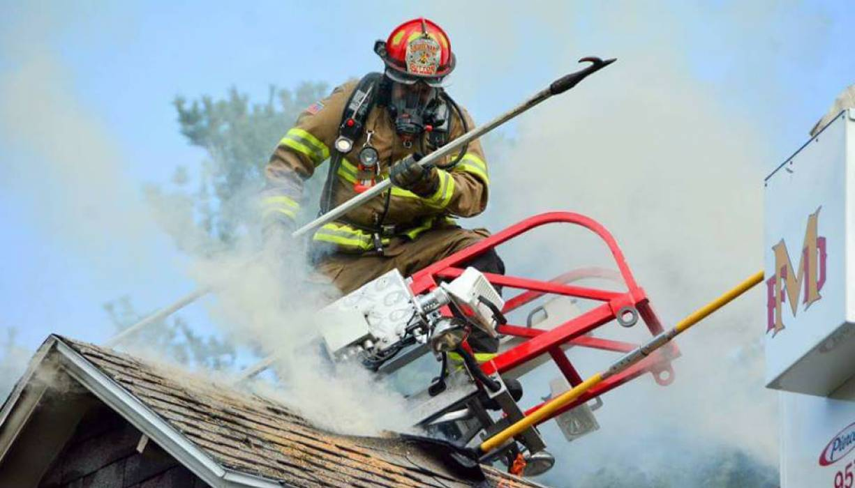 QCC Fire Science grad and Sutton firefighter Robin Dresser goes into action during a structure fire.