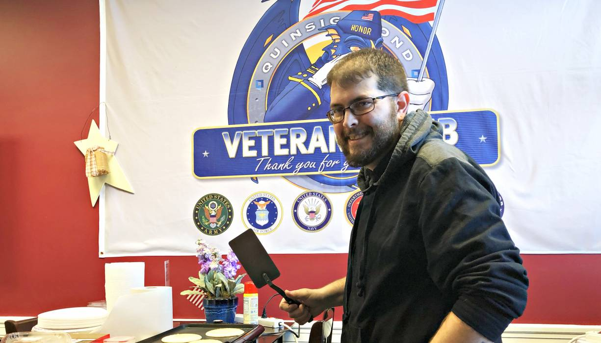 Mark Blease helps serve breakfast to QCC veterans.
