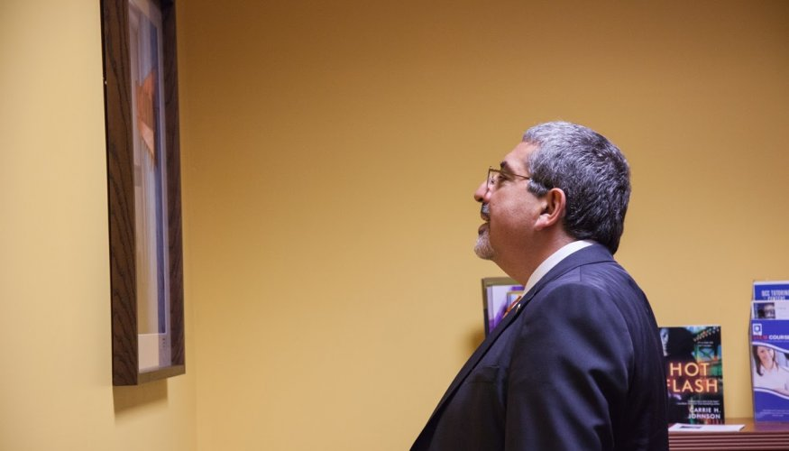 QCC's President admires the artwork on display.
