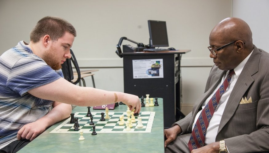QCC Chess Club Vice President Michael Imse plays a chess match with Chess Club Advisor Jerry Williams.