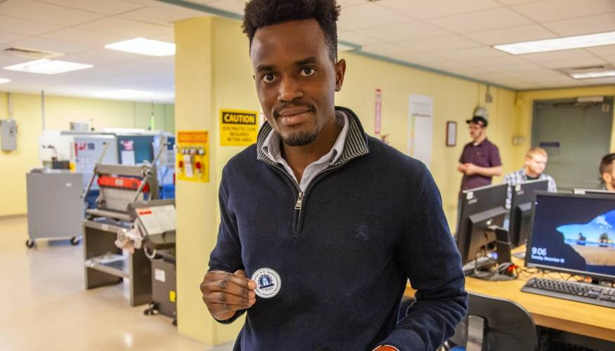 QCC student Dhalin Lutaaya shows off the challenge coin he earned.
