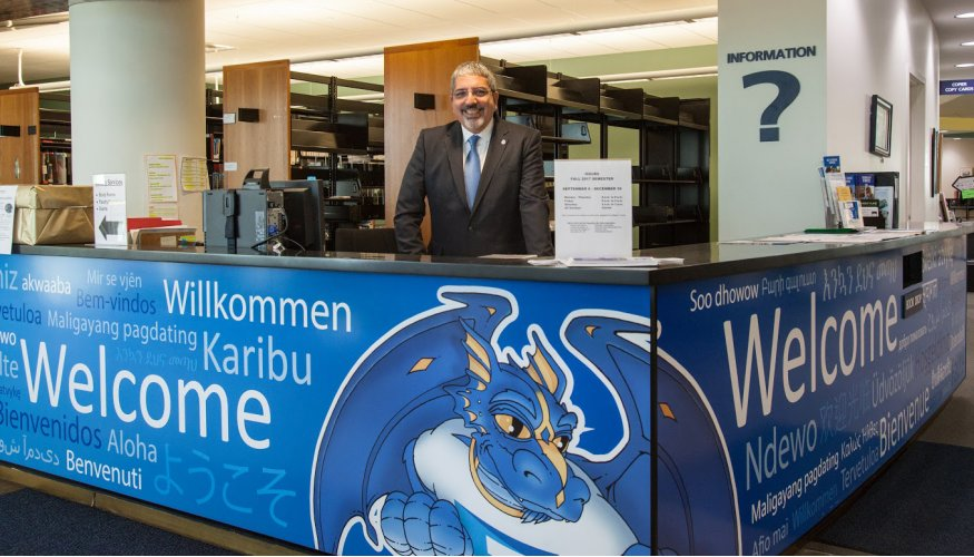 QCC President Dr. Luis Pedraja stands behind the counter of the new Welcome Center.