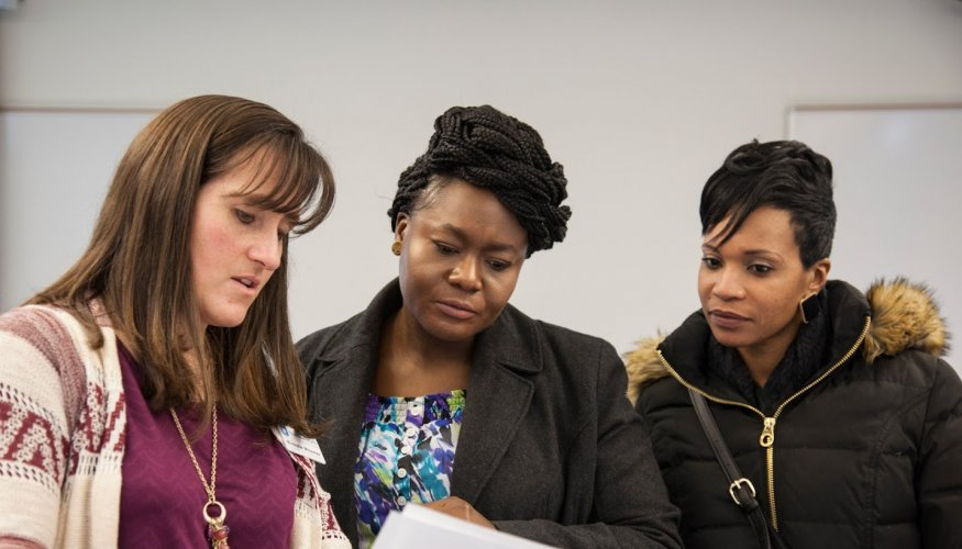 QCC Career Placement Representative Nichole Wheeler talks with QCC students at the recent Workplace Etiquette Luncheon.