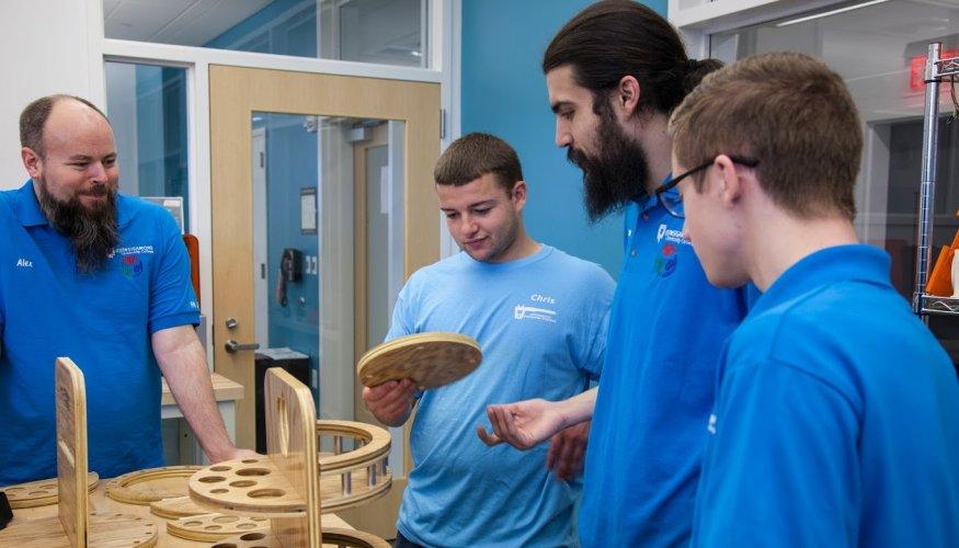 Manufacturing student Chris Bartczak (center) demonstrates his capstone project.