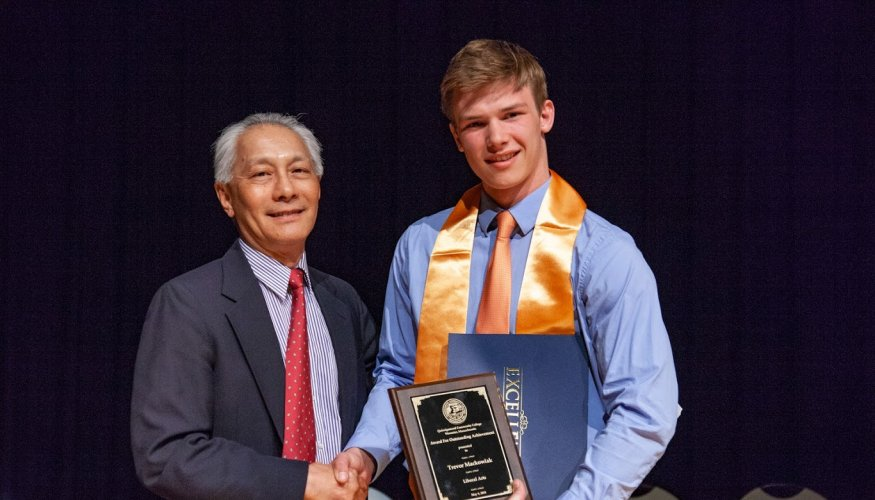QCC History Professor Ken Wong presents the award for Outstanding Achievement in Liberal Arts to Trevor Mackowiak.