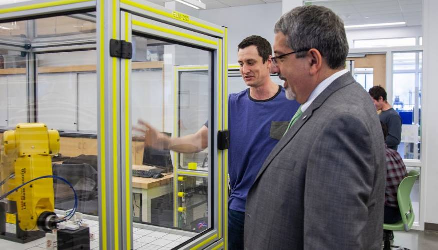 William Hogan (L) demonstrates the FANUC robot to QCC President Dr. Luis Pedraja.
