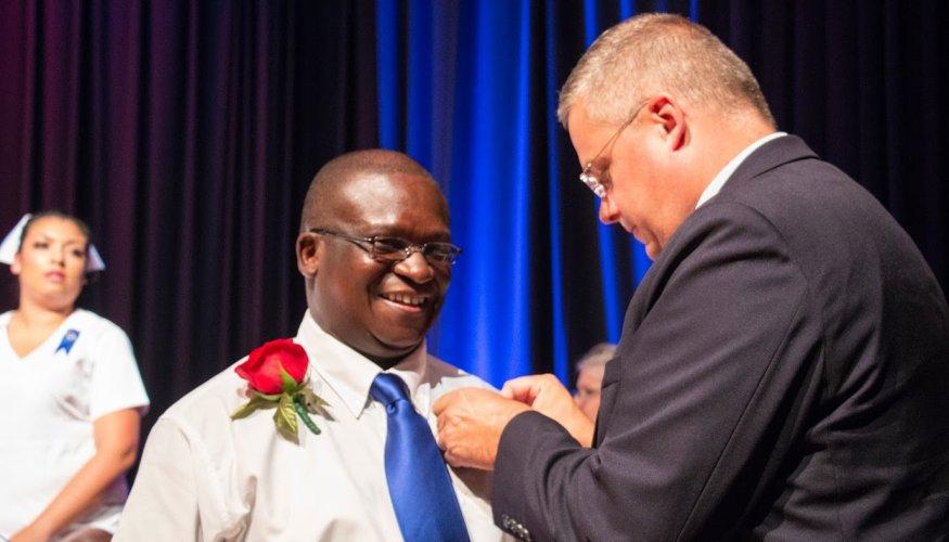Pat Schmohl, Dean of the School of Healthcare pins a recent PN graduate.
