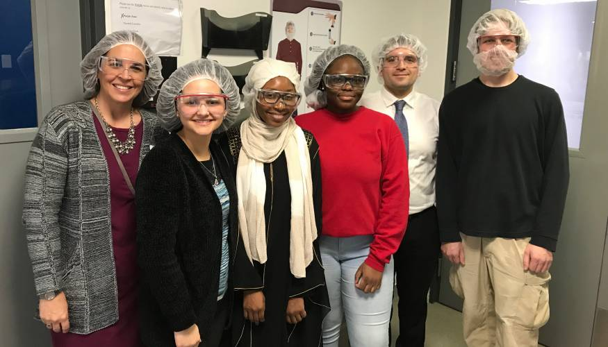 QCC staff member Selena Boria and Director of Mentoring Gabriel Santner (white shirt) tour AbbVie labs with QCC students.