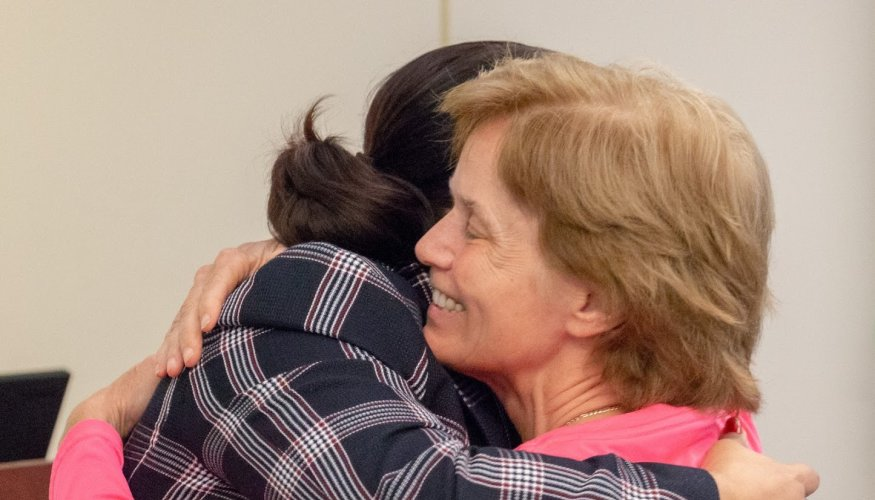 Vice President Lillian Ortiz gives a good-bye hug to Tara Fitzgerald-Jenkins.