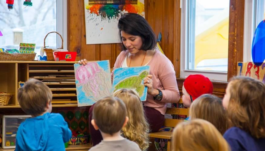 QCC Student Ana De la Torre talks to children at the Children's School.