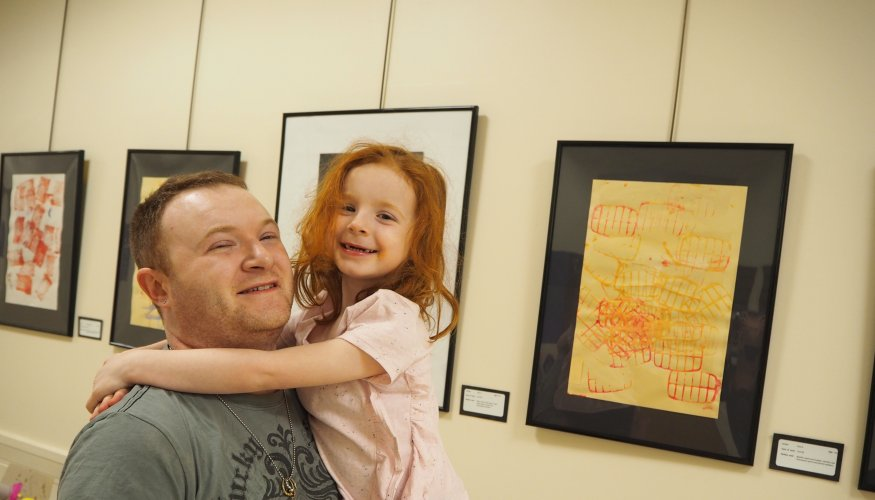 Alex and his daughter Zoe enjoy the art exhibit.