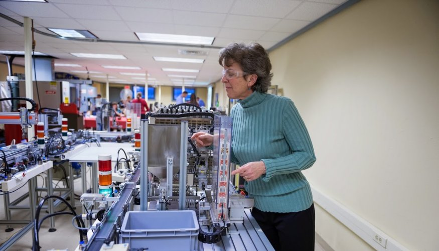 Kathy Rentsch, Dean of Business, Engineering and Technology at QCC checks out equipment in the Manufacturing lab.