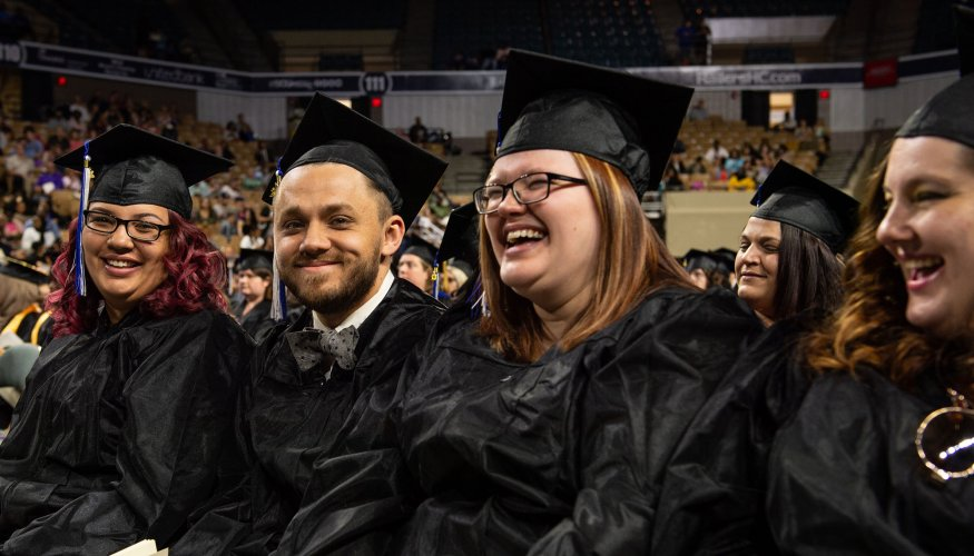 QCC grads can barley hold their excitement in as they wait to receive their degree or certificate.