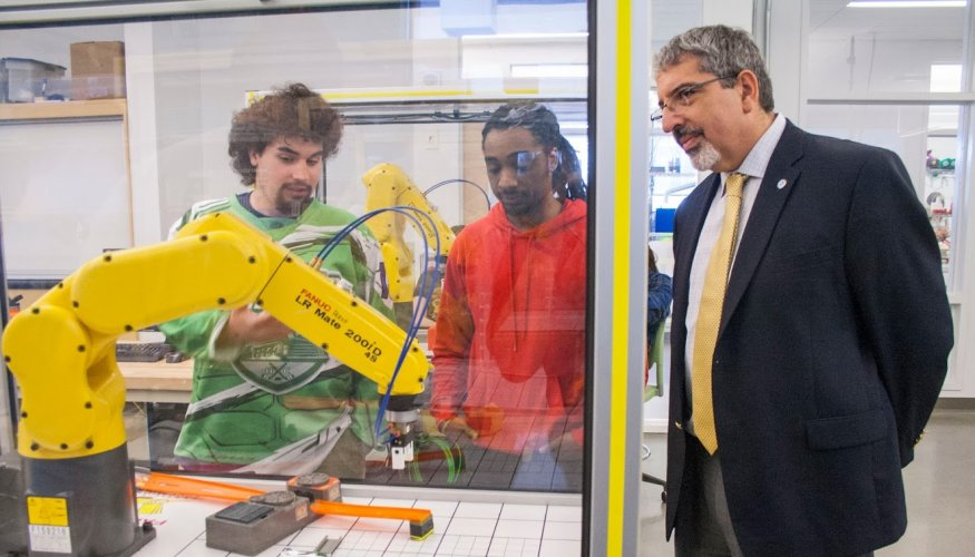 Dr. Luis Pedraja watches students Shawn Reese and Christian Hulett's robotic demonstration.