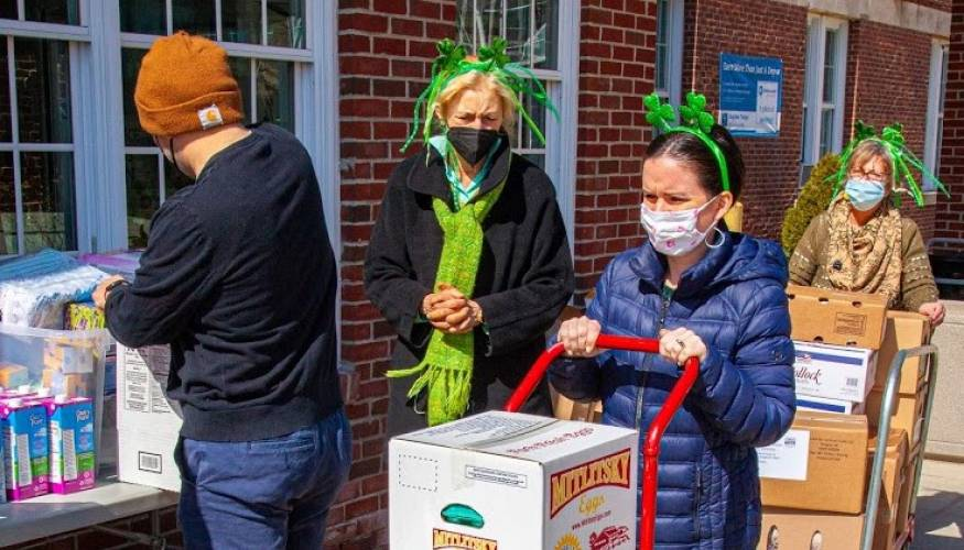 QCC's Food Pantry volunteers add a little St. Patrick's Day cheer to the weekly curbside food service for students in need.
