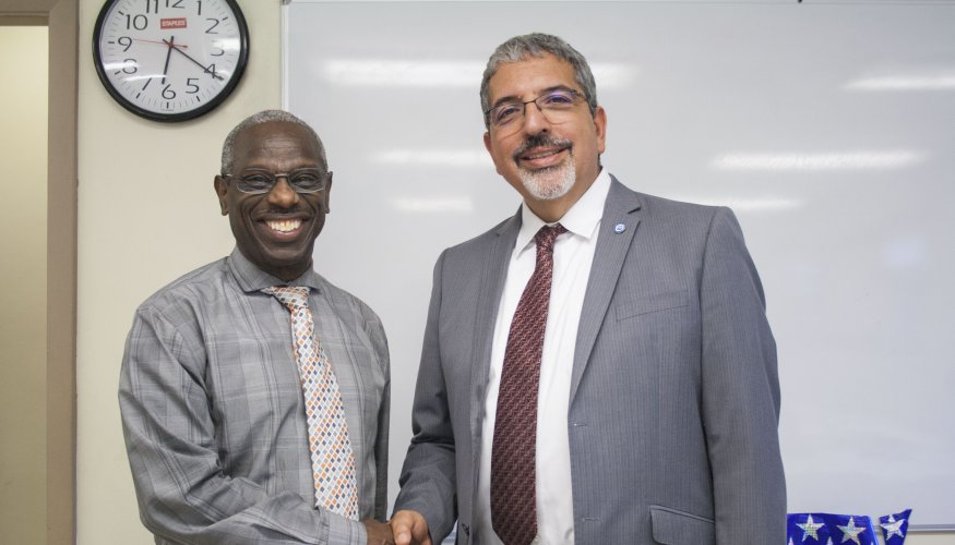 Carlton Watson, Director of Family and Resident Services at GBV (left) shakes hands with QCC President Dr. Luis Pedraja.
