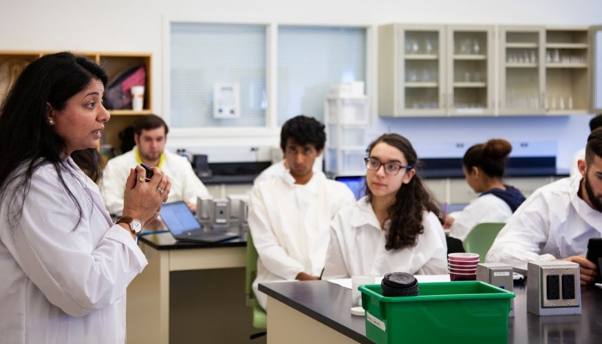 Chemistry Coordinator Hirul Patel discusses an experiment with her students.