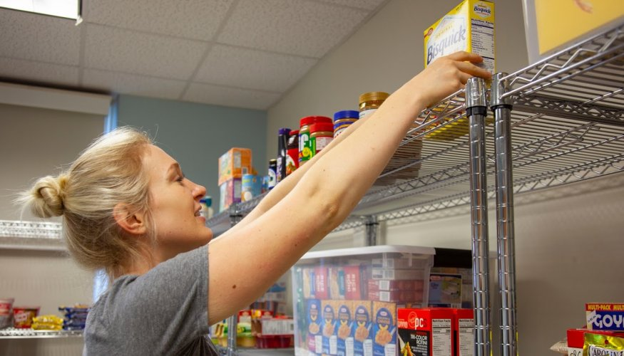 PTK student Vanessa Hanger works to stock the shelves at QCC's Food Pantry.