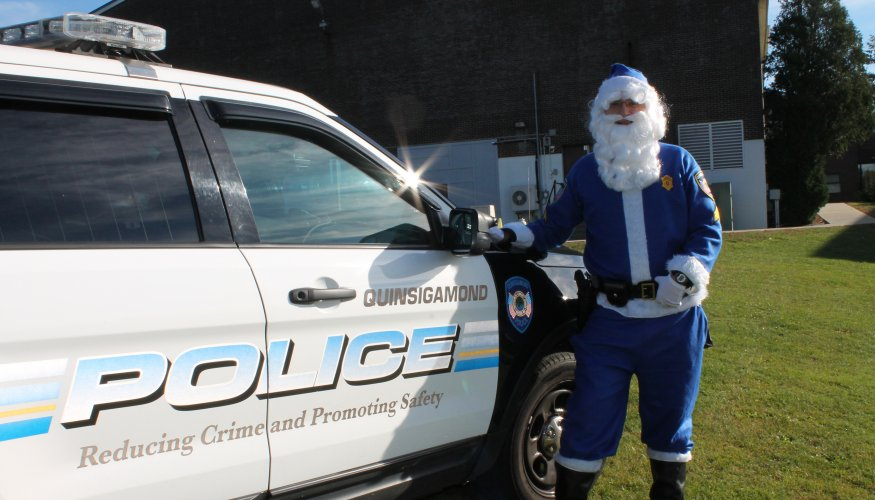 QCC officer dressed as Santa for Stuff a Cruiser