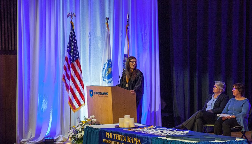 QCC student and outgoing PTK President Maia Shalev speaks at the recent PTK Induction ceremony as Dean of Student Theresa Vecchio (left) and PTK Advisor Bonnie Coleman look on.