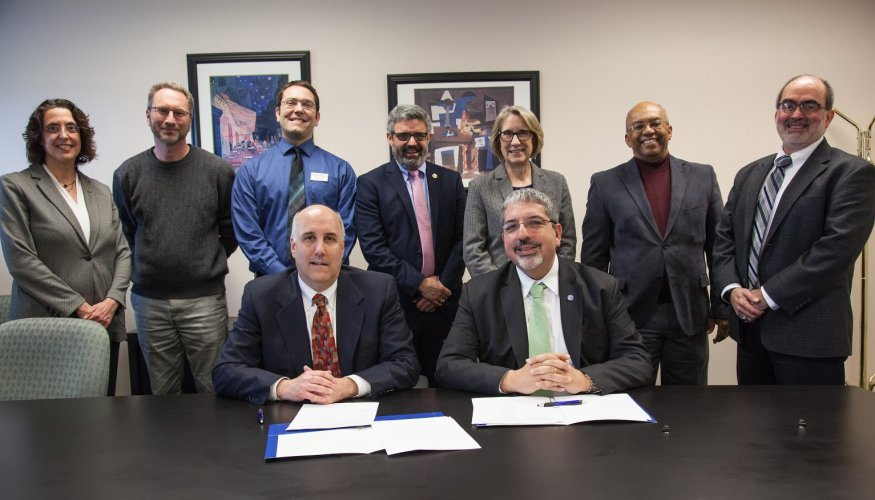From left (front): Fitchburg State President Richard S. Lapidus and Quinsigamond Community College President Dr. Luis. G. Pedraja sign Deaf Studies articulation agreement with faculty and staff from both college's in attendance.