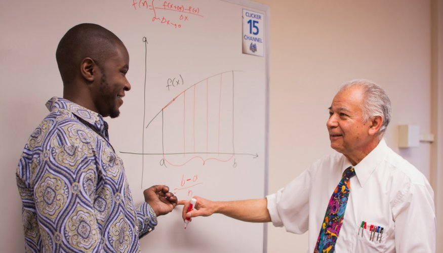 Dadbeh Bigonahy, Professor of Engineering & Sciences (right) demonstrates a math concept to a student.