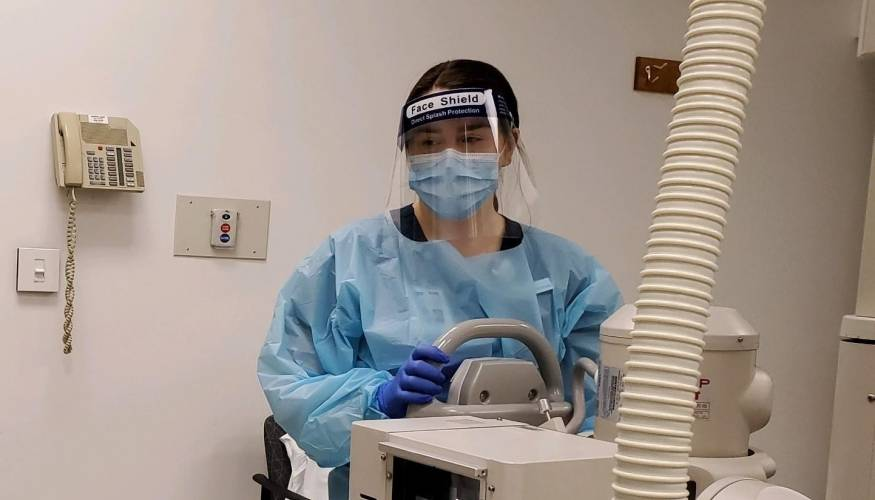 QCC Radiologic Technology student Holly Rank, of Westminster (wearing QCC provided PPE) practices image positioning.