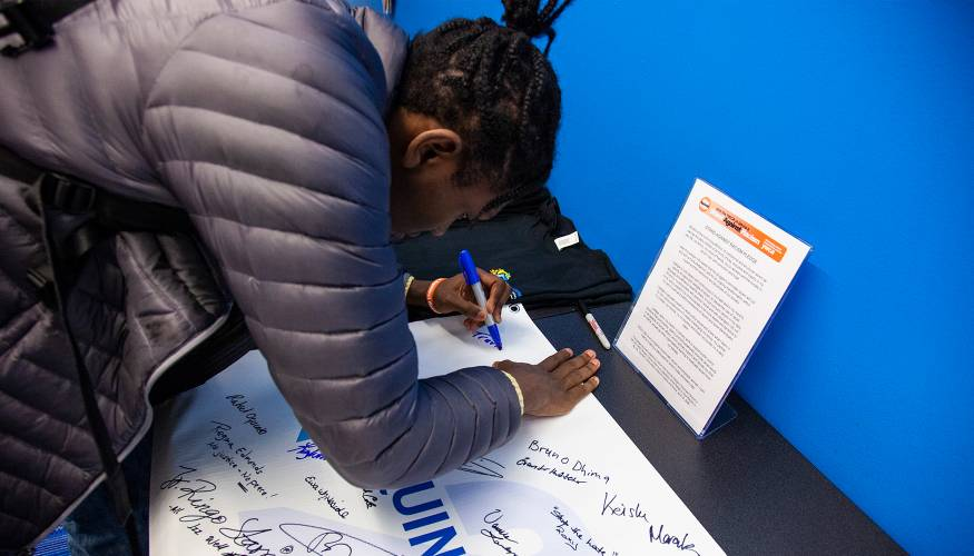 QCC students sign the Stand Against Racism banner to promote their stance against racism.