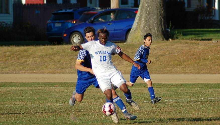 QCC soccer player Samuel Museme powers the ball forward.