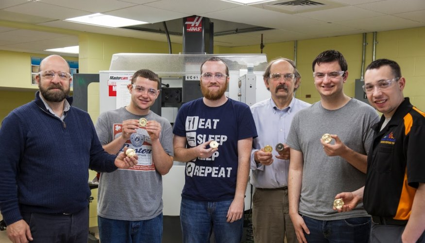 Associate Professor Duerden, QCC students and Dr. Goulet show off the new train wheels the students created.