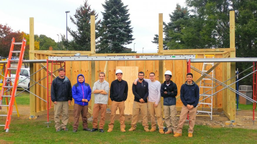 Worcester Technical High School carpentry students and their teacher at the partially constructed new dugouts.