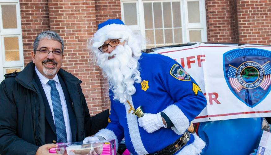QCC President Dr. Luis Pedraja drops off a toy for the Stuff-A-Cruiser event.